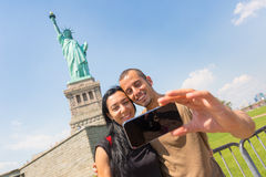 Couple Taking a Selfie with Statue of Liberty royalty free stock photos