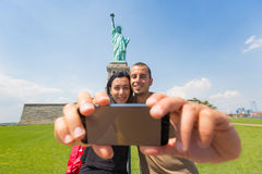 Couple Taking a Selfie with Statue of Liberty stock images