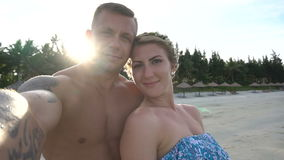 Couple taking selfie using phone on beach smiling, enjoying vacation stock video footage