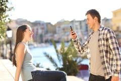 Couple taking selfies on vacation. Couple taking selfies on summer vacation in a coast town street royalty free stock image
