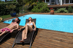 Couple taking sun by the swimming pool Royalty Free Stock Images