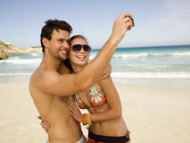 Couple taking their pictures on the beach Stock Photos