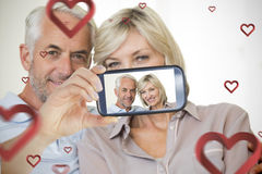 Couple taking Valentines selfie. Composite of Couple taking Valentines selfie Royalty Free Stock Photography