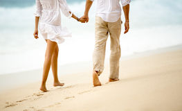 Couple taking a walk holding hands on the beach Stock Photo