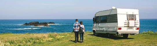 Couple taking a walk near the coast with a camper royalty free stock photography