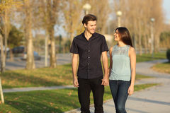 Couple taking a walk in a park. Happy couple laughing while taking a walk in a park Stock Photo