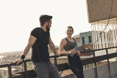 Couple taking a workout break. Young couple standing on a building rooftop terrace, taking a workout break royalty free stock photo