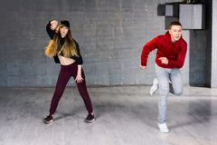 Couple of talented dancers performing hip-hop. Guy and girl dancing contemporary dance i studio. School of hip-hop culture Royalty Free Stock Photography
