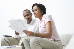 Couple Talking About Bills. Worried African American couple looking at bills Stock Image