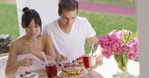 Couple talking at breakfast table outside. Young couple talking together over breakfast waffles at outdoor table with pink flowers in vase and green grass in stock video