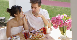 Couple talking at breakfast table outside Royalty Free Stock Photos