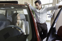 Couple talking in car show room Stock Photography