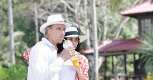 Couple Talking Drink Juice Under Palm Trees, Happy Man And Woman Tourist Communication On Tropical Vacation stock footage