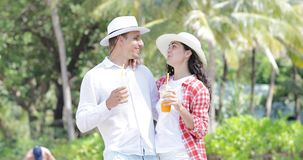 Couple Talking Drink Juice Under Palm Trees, Happy Man And Woman Tourist Communication On Tropical Vacation. Slow Motion 60 stock video