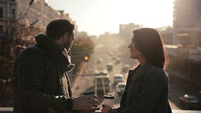 Couple talking and drinking coffee on a  bridge. Beautiful young couple talking and drinking coffee on a city bridge stock footage