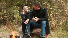 Couple talking and drinking near fire. Couple near fire talking and drinking tea or coffee stock footage