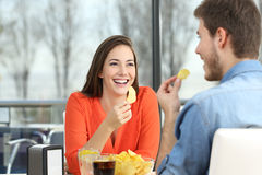 Couple talking and eating chip potatoes Stock Images