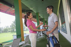 Couple talking and flirting on the golf course, holding a golf club Stock Photography