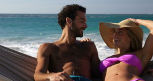 Couple talking in hammock. At the beach stock video