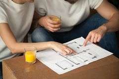 Couple talking about interior design with home plan, closeup vie. Couple talking about interior design with home plan, men and women discuss renovation ideas royalty free stock image