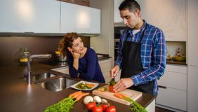 Couple talking while the husband cuts vegetables Royalty Free Stock Photography