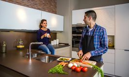 Couple talking while the husband cuts vegetables Royalty Free Stock Image