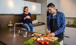 Couple talking while the husband cuts vegetables Stock Images