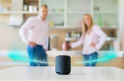 Couple talking and listening to smart speaker at home stock images