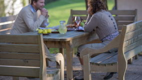 Couple talking before the lunch outdoors in urban scenery. Close up RAW footage of a couple seating behind the wooden eating table and talking before having the stock footage