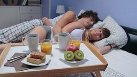 Couple talking lying in bed behind of breakfast on stock footage