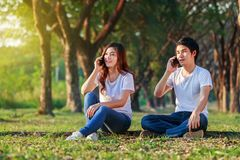 Couple talking on mobile phone in the park. Young couple talking on mobile phone in the park stock photos