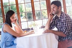 Couple talking on mobile phone in restaurant. Young couple talking on mobile phone in restaurant stock image