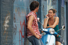 Couple Talking BY Moped By Wall. Cheerful young women on moped talking to men against wall Royalty Free Stock Photos
