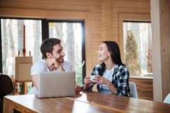 Couple talking near table with laptop stock photography