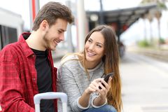 Couple talking about online content in a phone. Happy couple talking about online content in a smart phone in a train station royalty free stock images