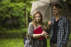 Couple  talking outdoors. Girl with a red book in his hands and the guy with the umbrella. Royalty Free Stock Photo