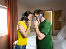 Couple talking by phones. Angry men and women talking by mobile phones in the room Royalty Free Stock Images