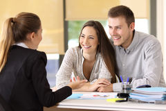 Couple talking with a real estate agent. Happy couple talking with a real estate agent at office stock photos