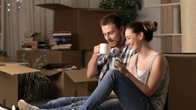 Couple talking and resting moving home in the night stock footage