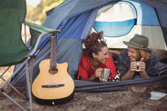 Couple talking while relaxing in tent Stock Images