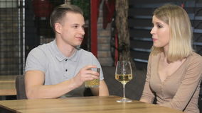 Couple talking at the restaurant. Young couple having a date at the restaurant. Blonde man drinking strong drink while blonde girl drinking white wine stock video