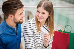 Couple talking about shopping. A photo of young, happy couple at the mall. The girl is holding a debit card Stock Photos