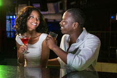 Couple talking and smiling while having drinks at bar counter. In bar Royalty Free Stock Photography