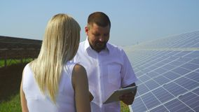 Couple talking at solar power plant. Man and woman talking at solar power plant. Girl interviewing a man at solar electricity station. Generation of clean stock video footage