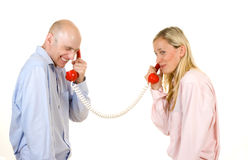 Couple talking on telephone. Happy young couple connected with red retro style telephones; white studio background royalty free stock photos