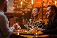 Couple talking to bartender behind bar counter in a cafe royalty free stock photography