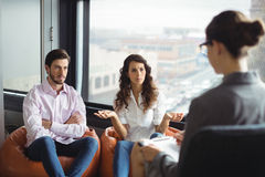 Couple talking to a marriage counselor during therapy. Annoyed couple talking to a marriage counselor during therapy Royalty Free Stock Photo