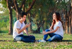 Couple talking and using mobile phone in park. Couple talking and using mobile phone in the park Stock Images