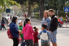 A couple with Vietnamese children. A couple are talking with Vietnamese children on a sunny street Stock Photo