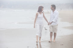 Couple talking while walking on a foggy beach smiling at each ot Stock Images